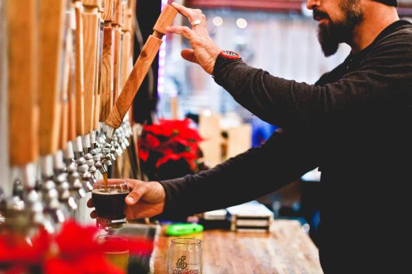 Man pours a pint at Strange Land Brewery