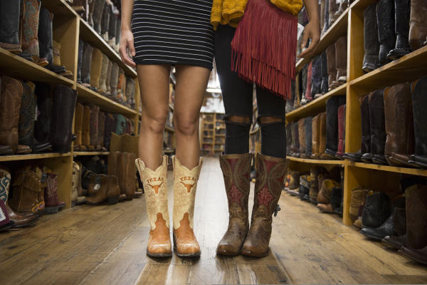 Two women model boots at Allens Boots on South Congress