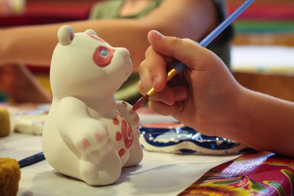 Painting a ceramic bear.
