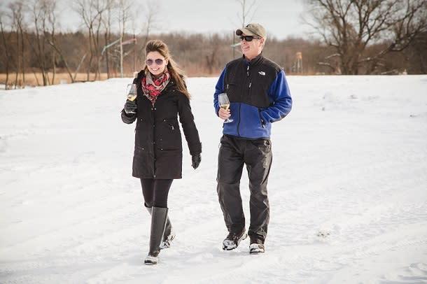 Couple walking through vineyard in winter