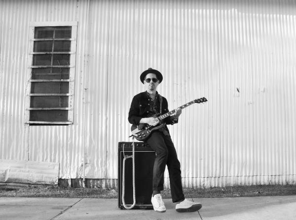 Adrian Quesada portrait with guitar sitting on amp