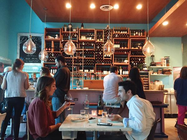 couple dining at aviary in front of bar and wine racks