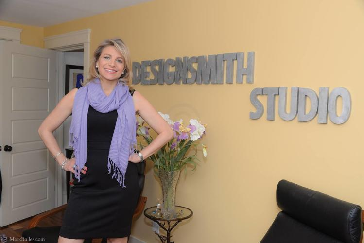 Designsmith Studio photo with owner posing in front of her name on the wall