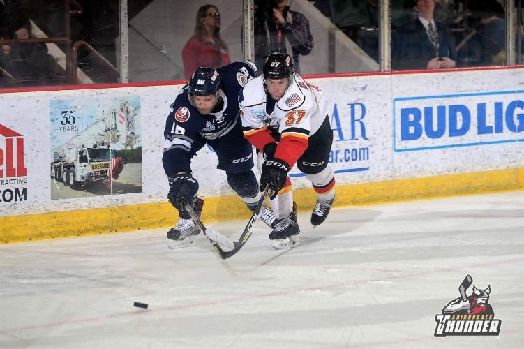 Adirondack thunder player and opponent going after the puck