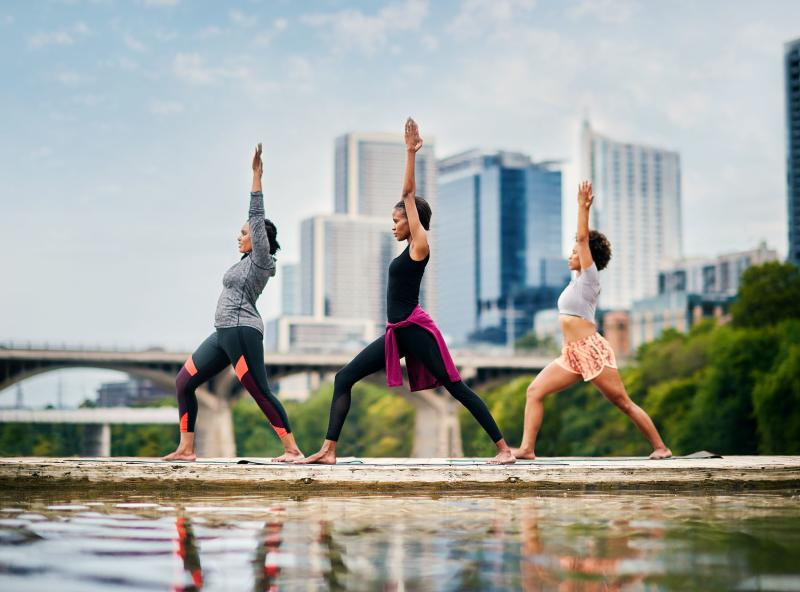 Three women practicing yoga on dock at Lady Bird Lake in Austin Texas