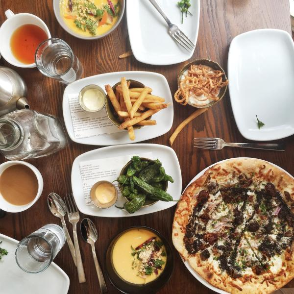 Table spread at Second Bar and Kitchen including pizza, fries, peppers and more