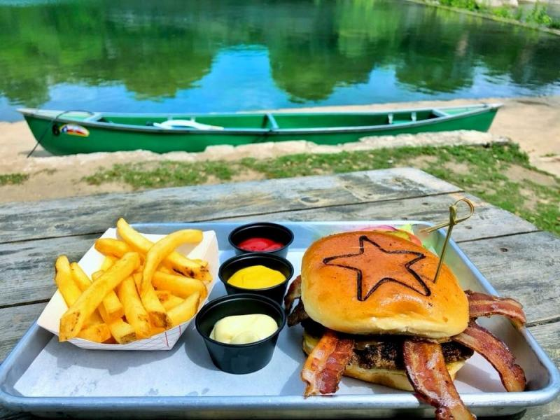 Bacon burger and fries on the dock in front of the river at The Back Porch in Wimberley Texas
