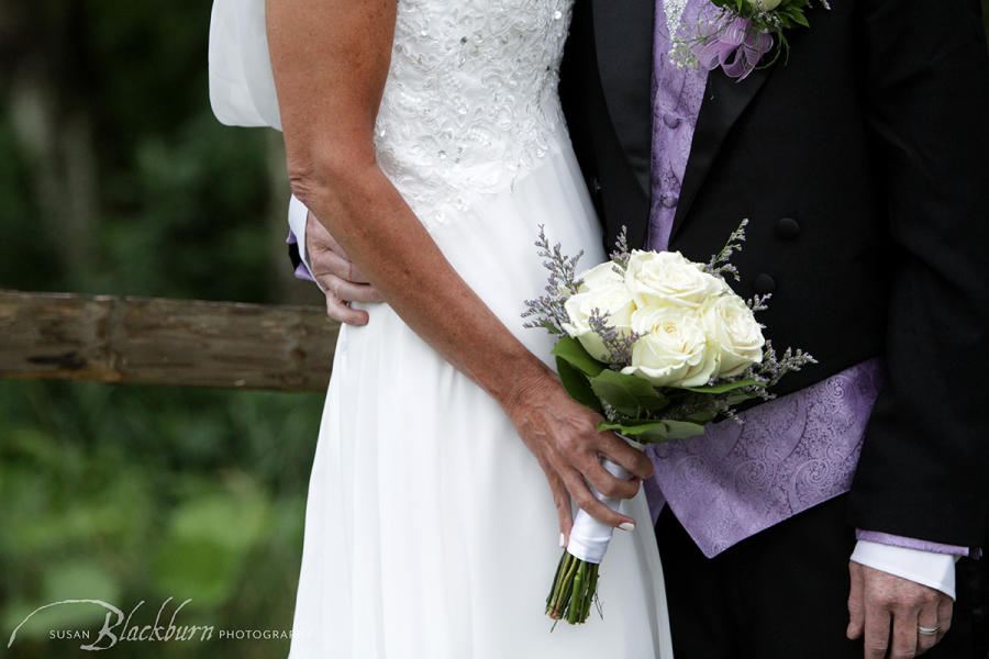 Couple holding white wedding bouquet with touch of purple