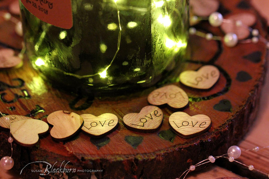 Bottom of wine bottle with lights and wooden hearts