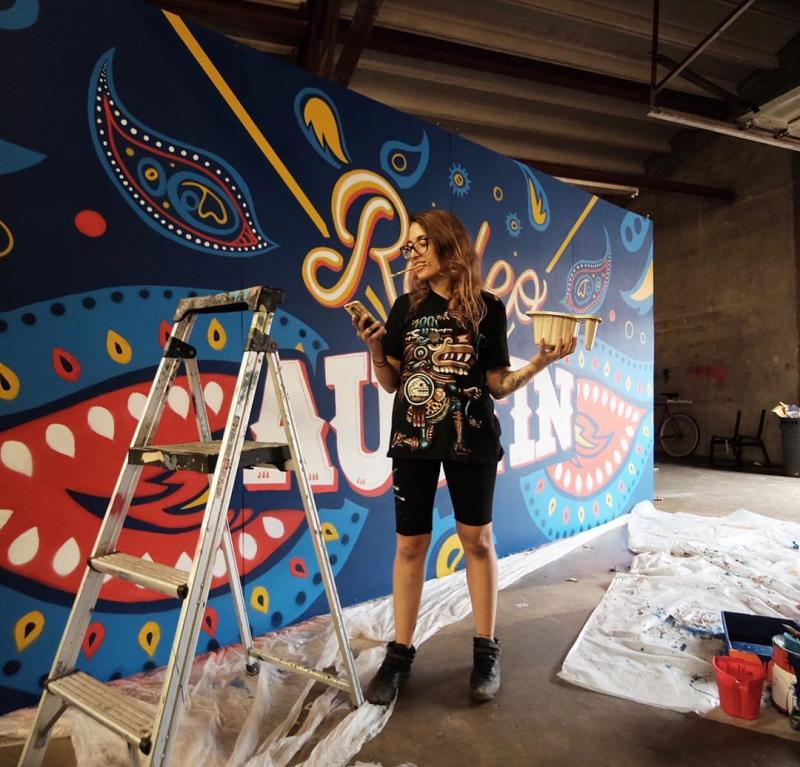 Artist painting mural at SprATX studio and creative agency in Austin Texas