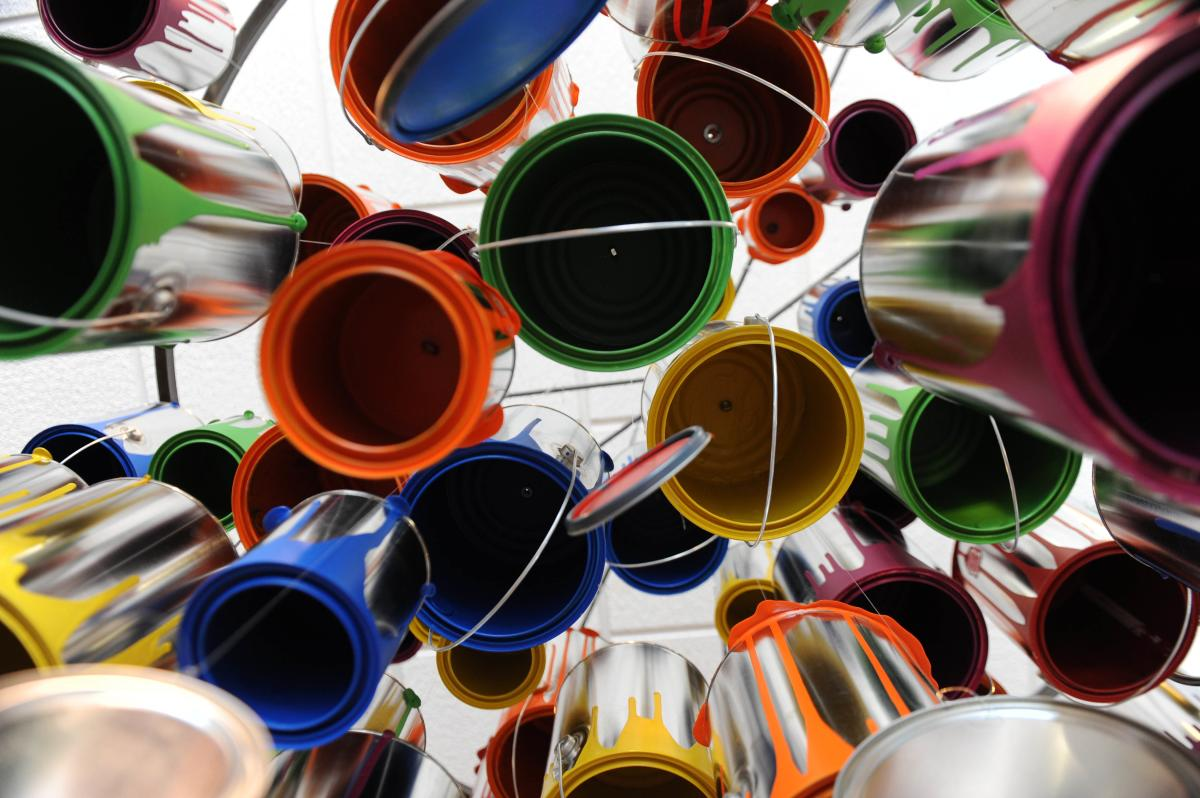 Art installation of multi-colored paint cans hanging from ceiling, photographed from below