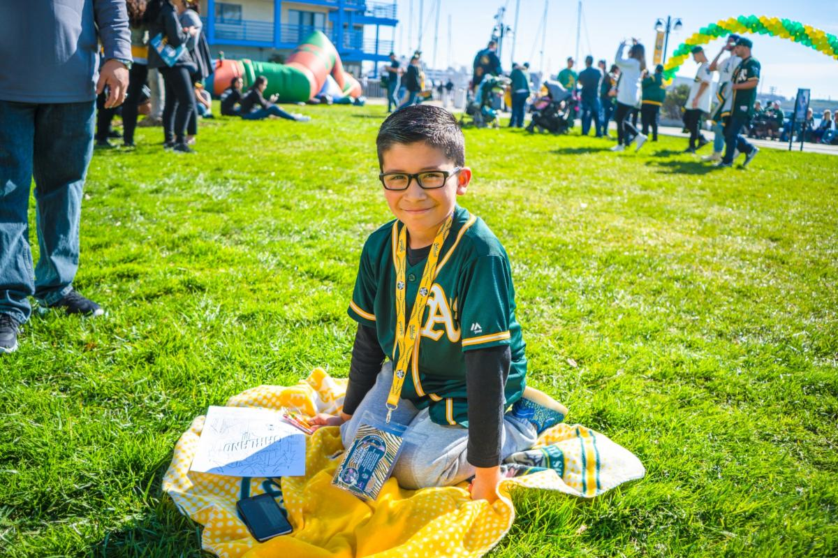 Child sitting in grass at Oakland A's game