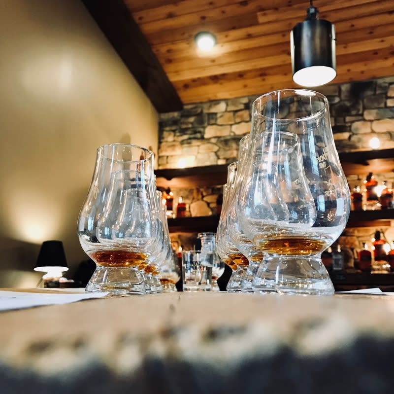 two rows of bourbon glasses holding a tasting flight of bourbon with a stone bar in the background