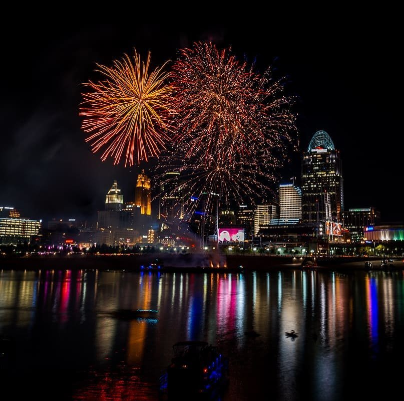 Several orange bursts of fireworks over Cincinnati seen from the Northern Kentucky riverbank on the Ohio