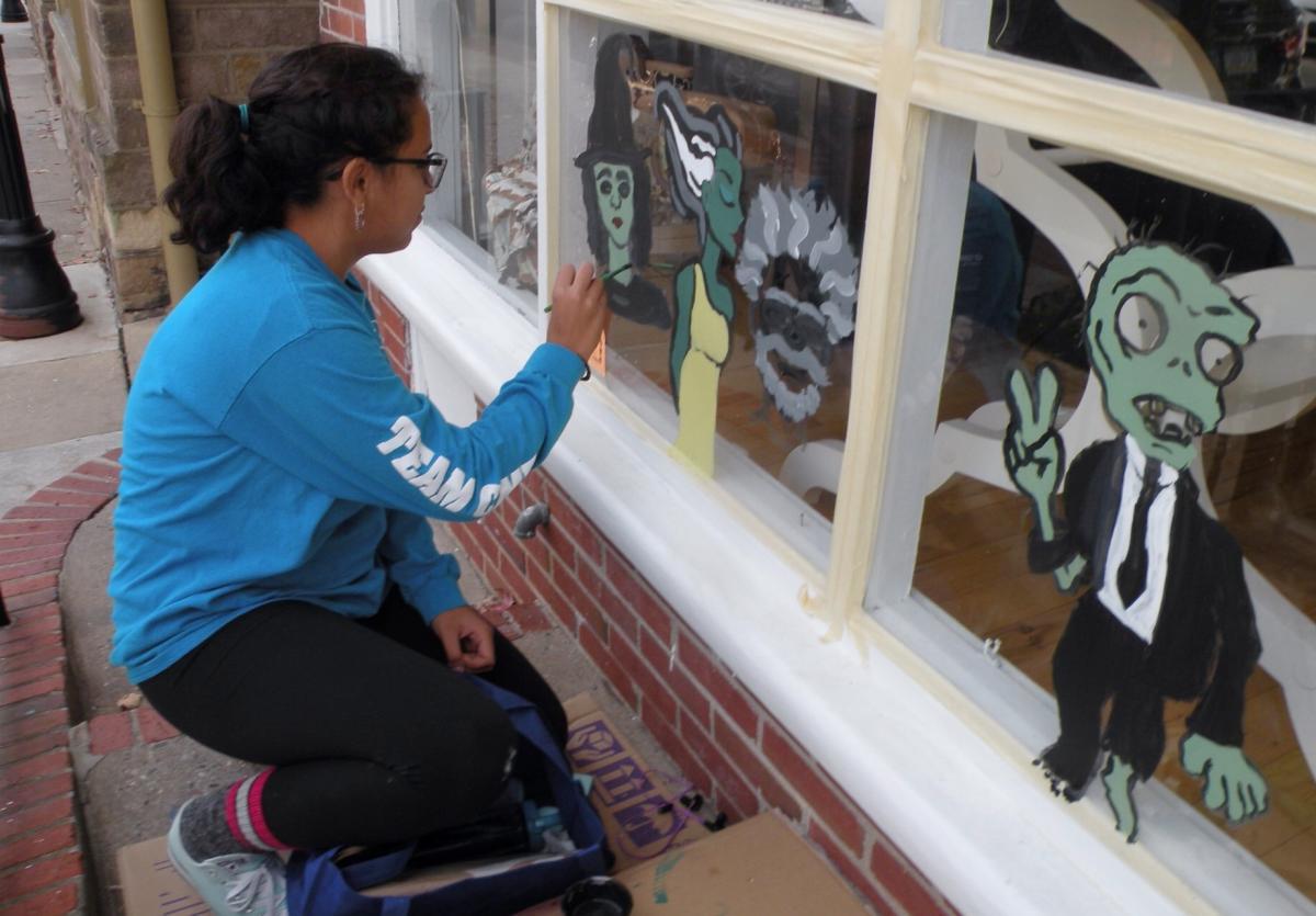 Woman painting Newtown window