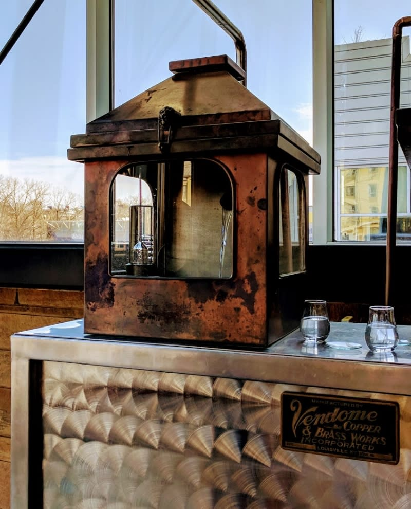 New Riff Distillery's copper and glass spirit safe with clear new make bourbon pouring out of it.