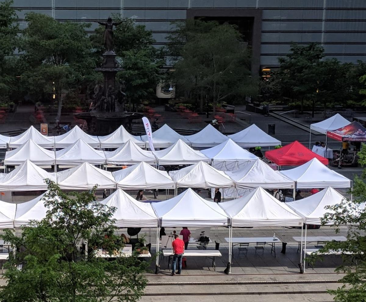 Rows of white tents on Fountain Square in Cincinnati with one red tent that reads