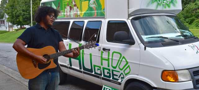 Musician Mike Martinez plays guitar as part of a Hood Tours experience.