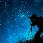 Man gazing at stars silhouetted against night sky