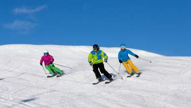 3 downhill skiers in the piste in Geilo