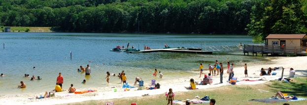 Visitors relax on the beach and enjoy swimming in the lake.
