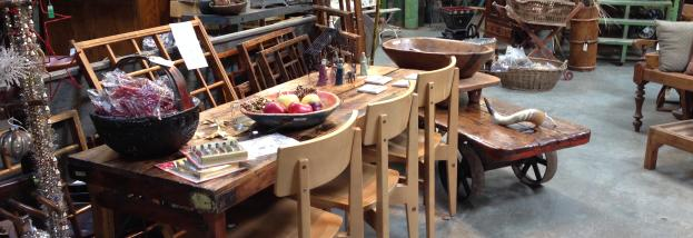 A table, chairs, and other home decor is presented in this warehouse style antique shop.