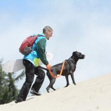 Sandboarding Sand Master Jam with a dog by Colin Morton