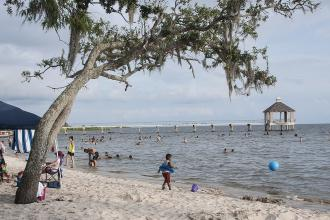 Visitors play on the beach at Fontainebleau State Park in Mandeville