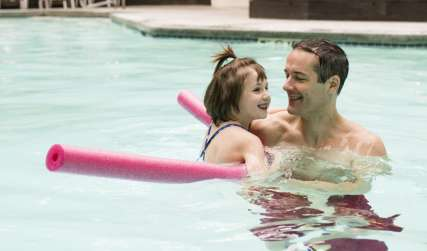 Father and Daughter playing in a pool
