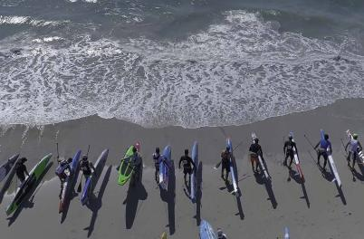 Lineup of standup paddleboarders on Wrightsville Beach preparing for start of race