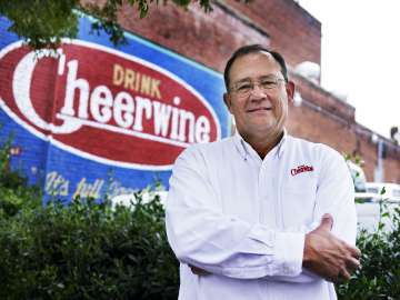 CEO of Cheerwine in front of Cheerwine building