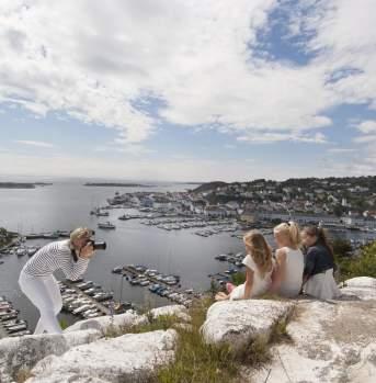 Woman photographing children at Risørflekken viewpoint in Risør