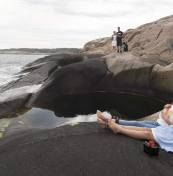 Girls sitting next to potholes by the sea