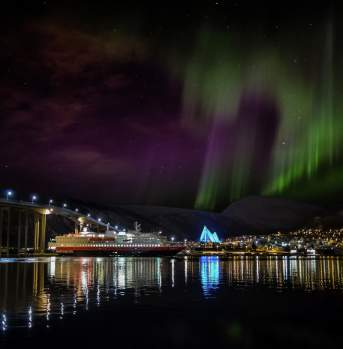 Tromsøysundet strait with Hurtigruten and the Arctic Cathedral under the northern lights