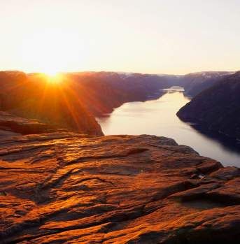 A person watching the sunrise at Preikestolen (The Pulpit Rock) in Ryfylke