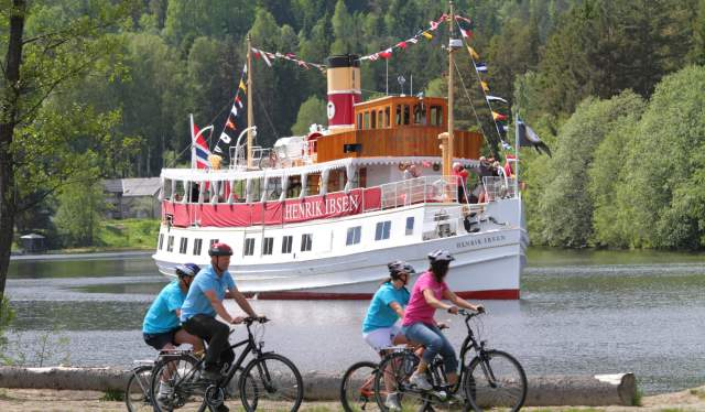 People on bikes at the Telemark canal with canal boat.