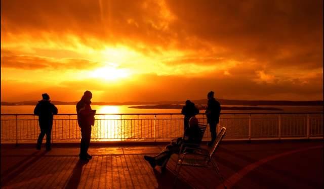 Soleil de minuit sur le pont de Hurtigruten, Norvège