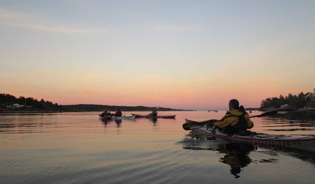 Three kayaks at sea by sunset