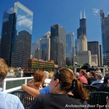 Passengers on a boat cruise look at buildings along the river edge