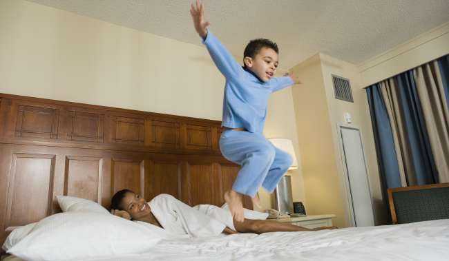Boy Jumping on Hotel Bed as Mom Watches