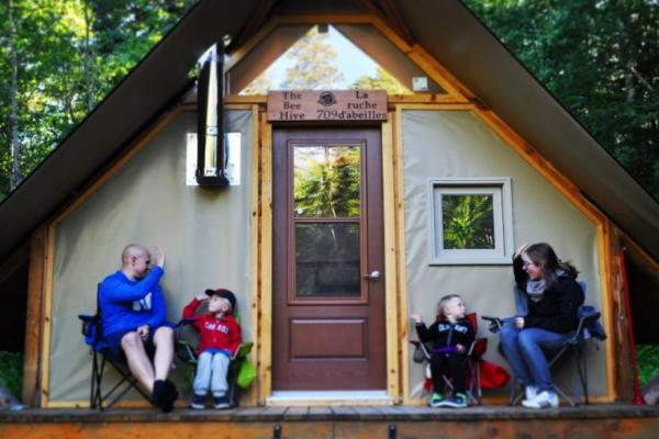 Family high fives on deck of oTentik, camping in Riding Mountain
