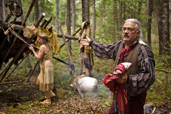 Guide dressed in traditional voyageur gear at a campsite