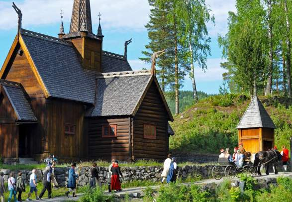 A group of people in old costumes walk past the stave church at Maihaugen, Lillehammer