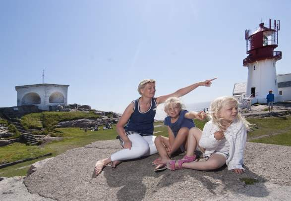 Woman and kids looking at something behind the camera, with the lighthouse in the background