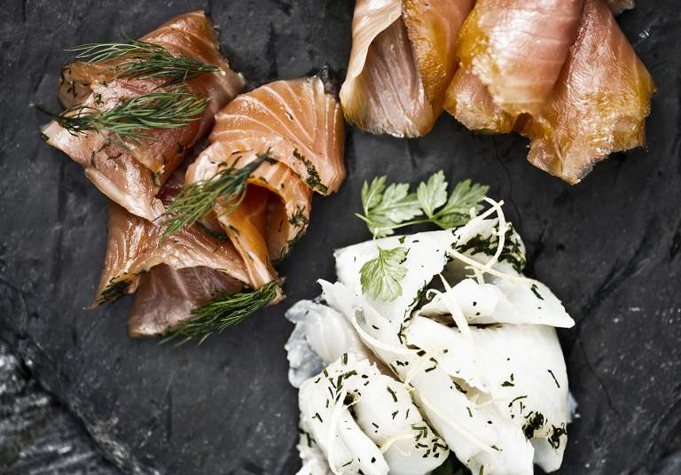 A stone platter with smoked salmon and other food
