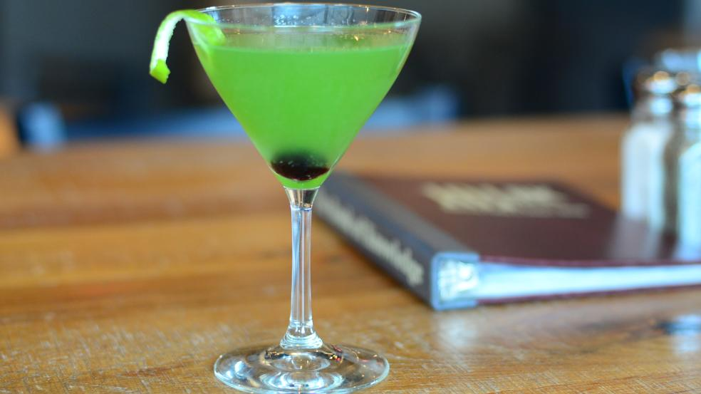 Bright green cocktail in a martini glass with cherry at borrom and lime twist garnish.