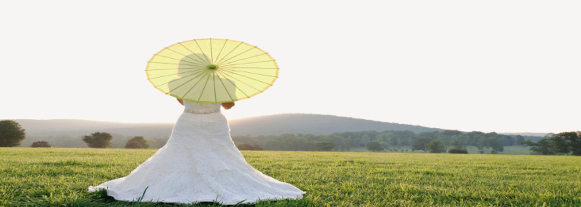 Bride holding parasol looking at a mountain view