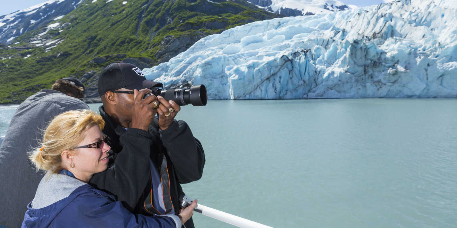Couple photographs Portage Glacier during glacier cruise