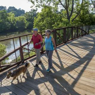 Couple walking dog along French Broad River Greenway