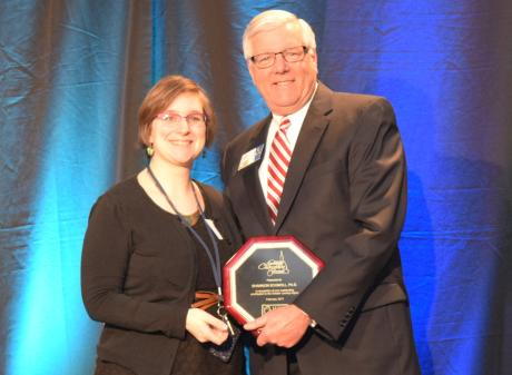Shannon Schmoll, Ph. D. accepts her Community Champion Award from Jack Schripsema